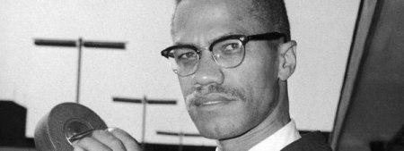 El activista estadounidense Malcolm X (1925 - 1965) sostiene una cámara de 8mm en el aeropuerto de Londres, en julio de 1964. GYI
